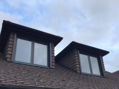 Image of two aluminium windows illuminating the top floor of the house.