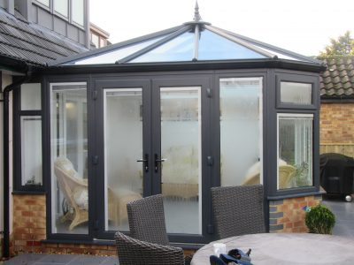 Outside view of a lovely new conservatory Livin room design with grey french doors.