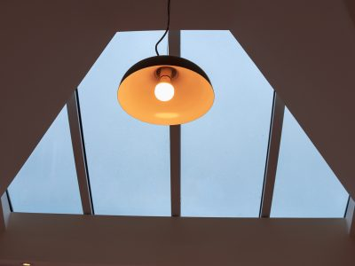 View of see through roof with warm hanging lamp.