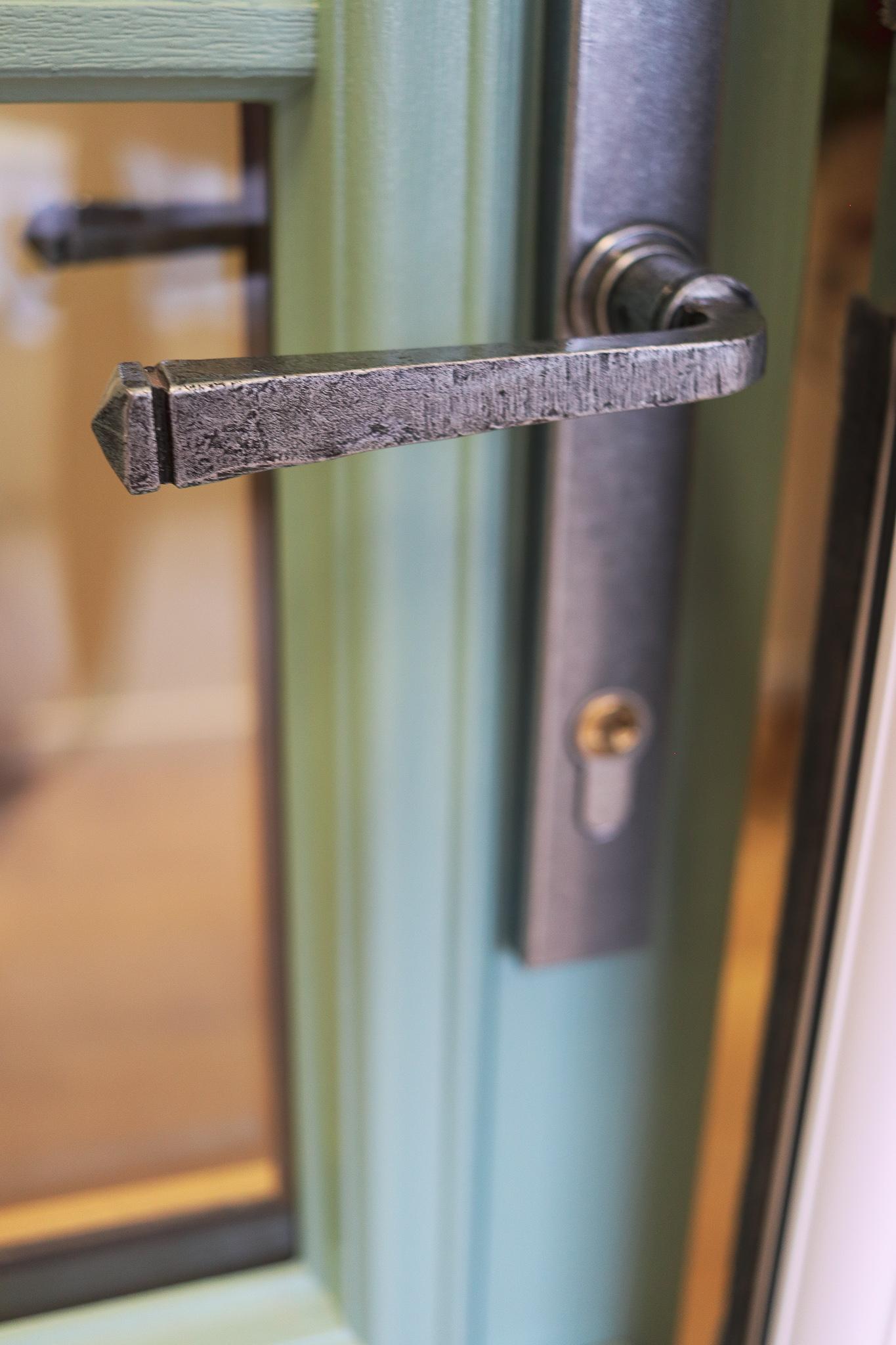 View of a door handle design surrounded by green door frame.