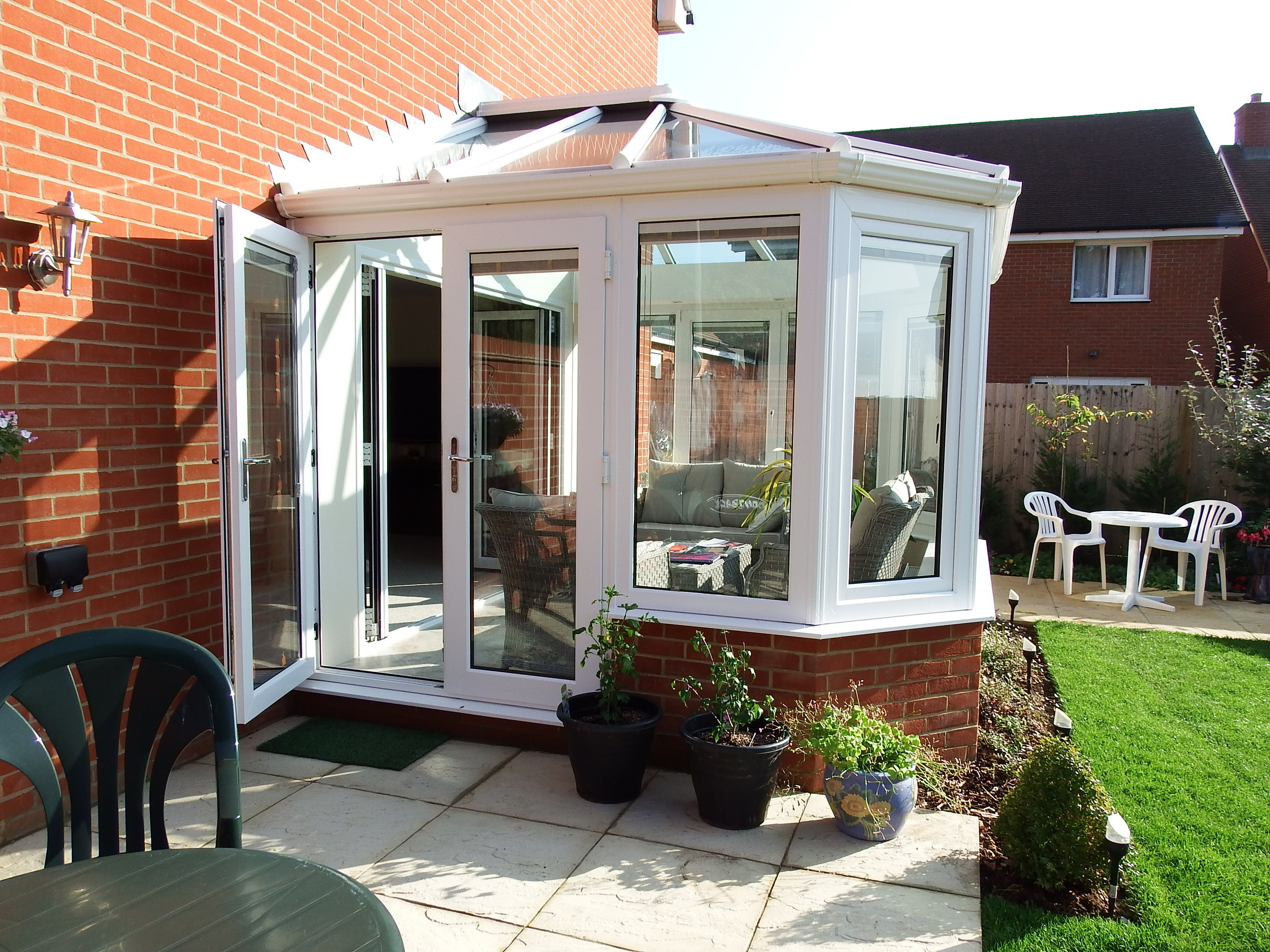 Side image of a Livin room conservatory with white french doors and windows.